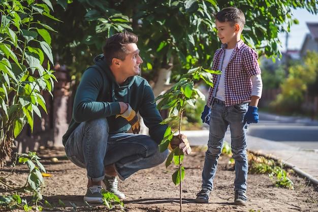 Отец и сын вместе занимаются садоводством