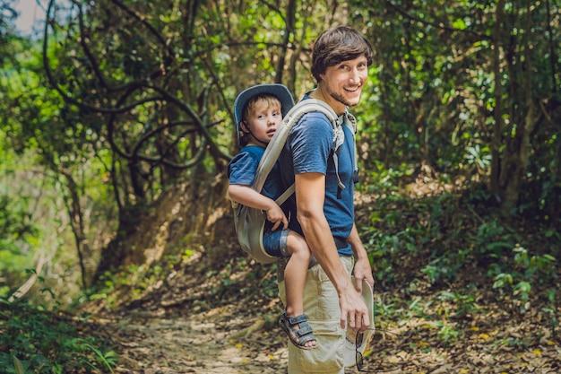 父親は息子を赤ちゃんに連れて行き、森でハイキングをしています。観光客はベトナムの自然の中で子供を背負っています。
