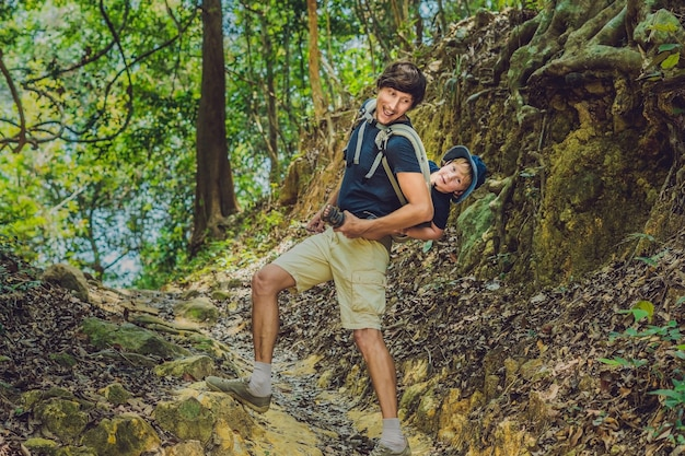 Отец несет сына с младенцем на руках в походе по лесу
