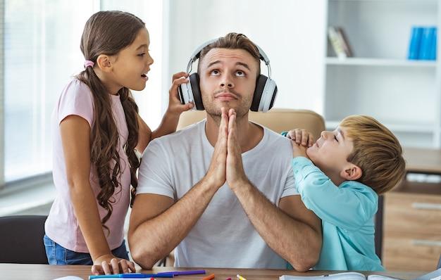 机に子供と一緒に座っているヘッドフォンの父