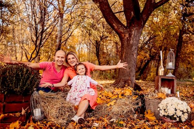 Отец, мать и дочь, сидящие на сенах