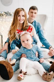 父、母はクリスマスツリーの近くに幼い息子と娘を抱きます。明けましておめでとうございます。クリスマスに飾られたインテリア。家族の休日の概念。閉じる。