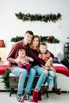 Отец-мать держит маленького сына и дочь возле елки концепция семейного отдыха