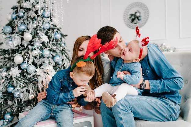 아버지, 어머니는 크리스마스 트리 근처에 작은 아들과 딸을 안고 있습니다.