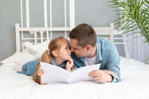 Отец читает книгу или занимается с ребенком дочери перед сном или развлекается.