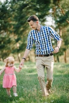 Отец бегает с дочерью и держит ее за руку на природе на летних каникулах. папа и девочка гуляют и играют в парке во время заката. понятие дружной семьи. крупный план.