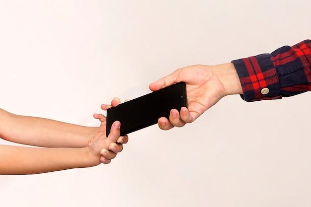 아버지는 딸에게서 전화를 받습니다. 아이들의 모바일 게임 중독. 도둑이 아이의 전화를 훔쳤습니다. 팔 클로즈업에 스마트폰입니다. 손에서 손으로 선물을 전달합니다.