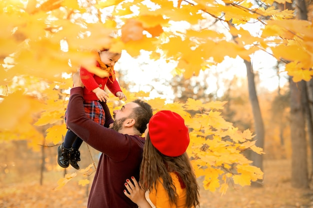 父は笑っている娘をカエデの枝のオレンジ色の葉に投げ込みます
