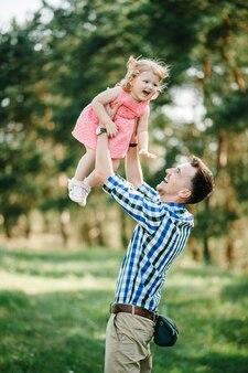 Отец рвет и раскручивает дочь на природе на летних каникулах. папа и девочка играют в парке во время заката. девушка летит. понятие дружной семьи. крупный план.