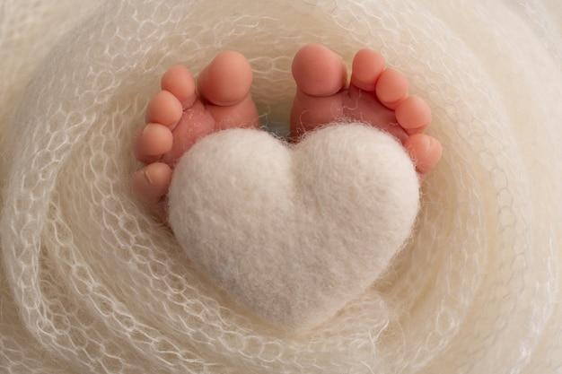 Ножки новорожденного укутывают вязанным пледом. пальцы новорожденного держат белое вязаное сердечко. фото высокого качества