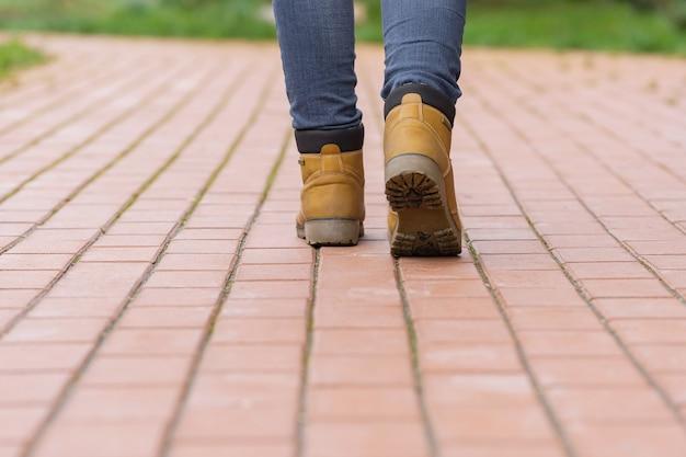 보도를 걷고있는 보행자의 발.