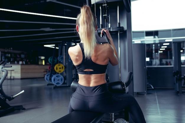 Спортсменка упорно тренируется в тренажерном зале. концепция фитнеса и здорового образа жизни.