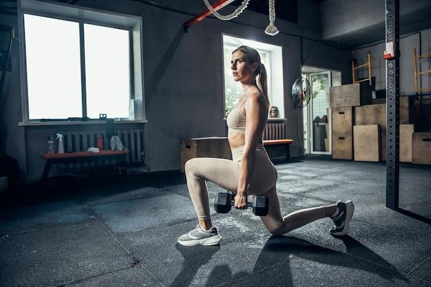 ジムのフィットネスと健康的な生活の概念で一生懸命トレーニングしている女性アスリート