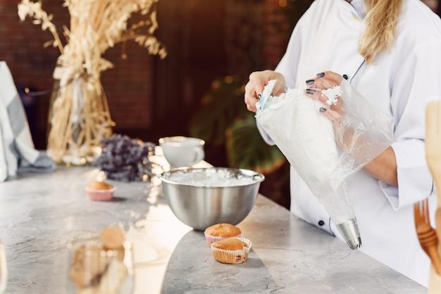 Женщина-кондитер наполняет кондитерский пакет свежеприготовленным кремом.