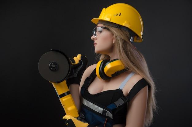 검정 배경 위에 앵글 그라인더가 있는 단단한 모자를 쓴 여성 건설 노동자