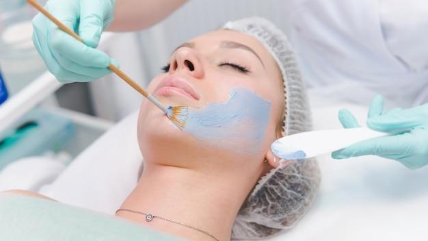 젊은 여성의 얼굴에 파란색 미용 마스크를 적용하는 여성 미용사, 클로즈업. 뷰티 클리닉의 얼굴 미용 치료. 피부와 건강 관리의 개념