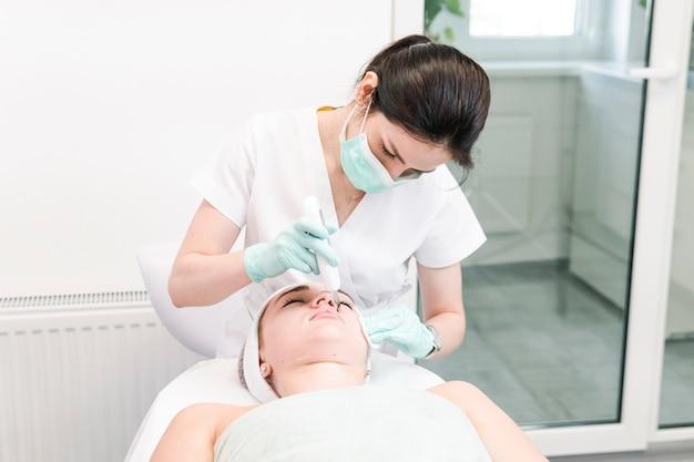 여성 미용사는 초음파 세척 얼굴 근접 촬영 절차를 만듭니다.