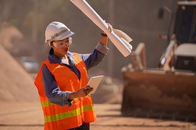 女性エンジニアがノートパソコンでの作業を検討し、道路建設の作業を計画しています。