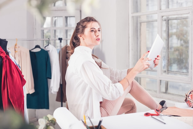 Женский модный дизайнер работает в студии, сидя на столе