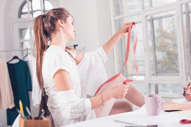 Модельер женского пола работает в студии, сидя на столе