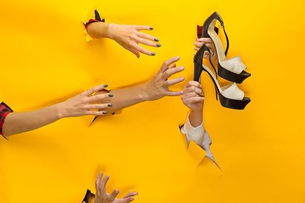分離された破れた紙を通して女性のサンダルを持っている女性の手