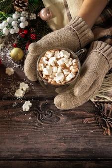 Женские руки варежки рождественские подарки и горячее какао с зефиром копирование пространства