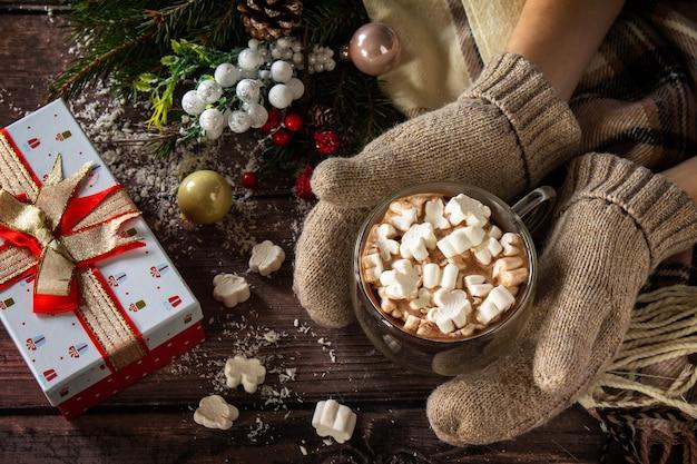 Женские руки варежки рождественские подарки и горячее какао с зефиром на деревянном столе