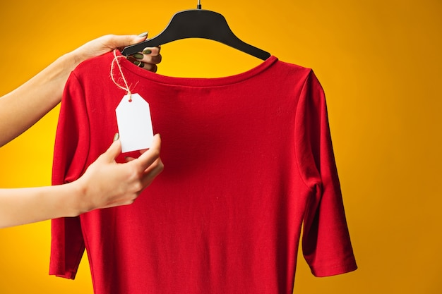 노란색에 드레스와 여성 손입니다. 쇼핑 및 판매 개념