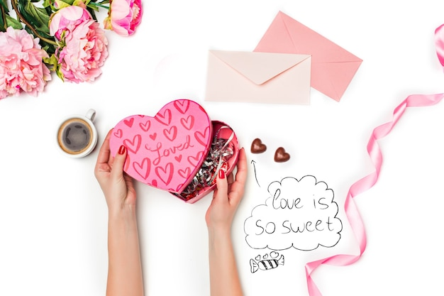 バラ、ギフトボックス、リボン、ハート、白い背景の上の紙とペンの空白のシートを持つ女性の手。幸せなバレンタインデーのコンセプト