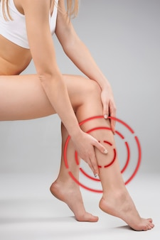 白い背景の上の女性の脚と手