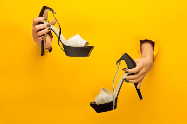 Женская обувь под рукой сквозь рваную желтую бумагу