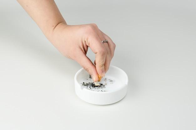 Женские руки тушат сигарету в пепельнице
