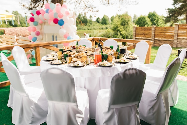 Праздничный богатый круглый стол с белой скатертью и стульями, поданный с различными блюдами и напитками, стоит на зеленой траве в банкетном зале на фоне деревянной усадьбы.