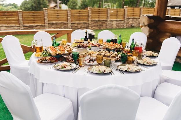白いテーブルクロスと椅子を備えたお祝いの豊富なラウンドテーブルは、さまざまな料理と飲み物を添えて、木製の荘園との結婚式の宴会場の緑の草の上に立つ