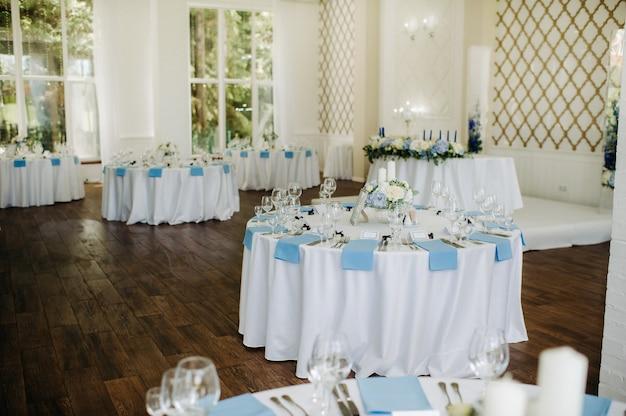 축제 테이블은 음식이 없는 파란색 냅킨과 꽃으로 밝은 색상으로 장식되어 있습니다.