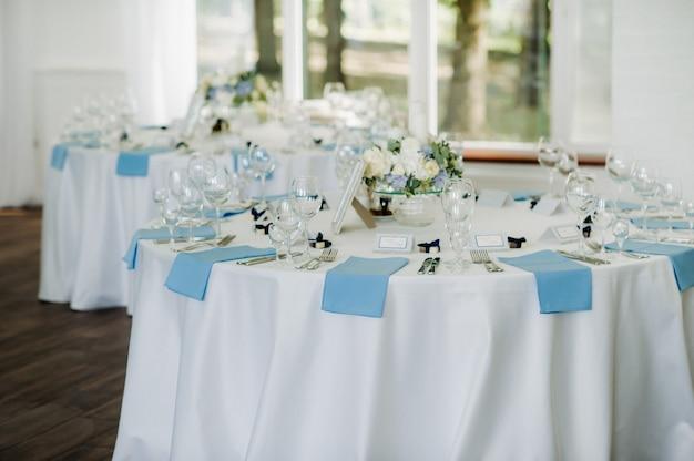 Праздничный стол оформлен в светлых тонах синими салфетками и цветами без еды.