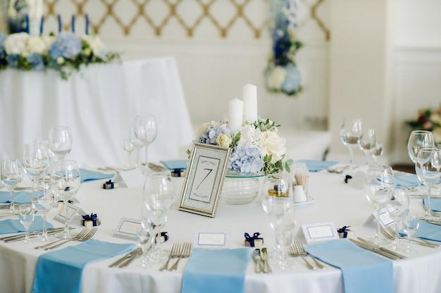 お祝いのテーブルは、青いナプキンと食べ物のない花で明るい色で装飾されています。