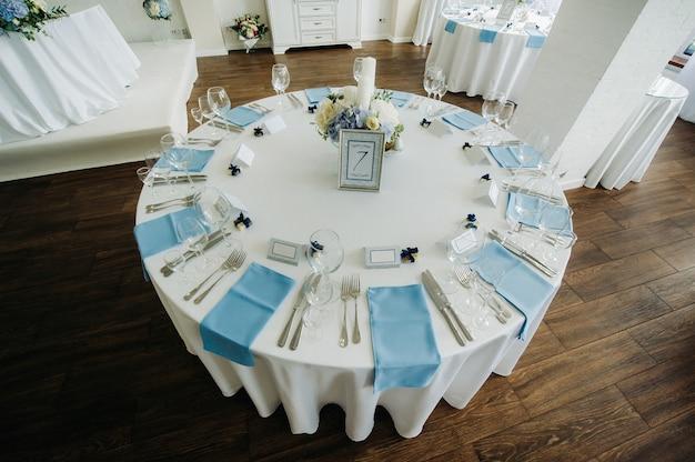 Праздничный стол оформлен в светлых тонах голубыми салфетками и цветами без еды.