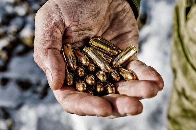 Боец держит в ладони пригоршню пуль для оружия. смешанная техника