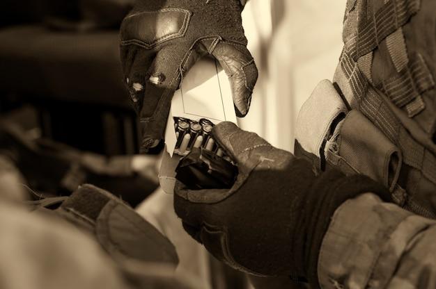 Перед следующим боем боец готовит обойму с патронами. смешанная техника
