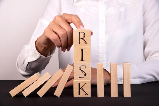 指は木製の立方体を保持しますリスク管理の概念
