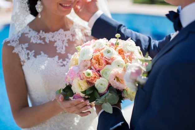 Первая встреча жениха и невесты в день свадьбы. эмоции молодоженов перед свадебной церемонией. жених и невеста смотрят друг на друга, обнимаются и целуются.