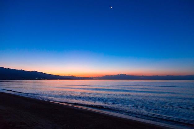 暗い夜空を背景に昇る太陽の最初の光線