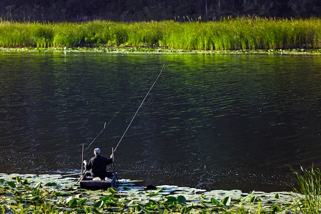 Рыбак у резиновой лодки. снято у пруда в россии.