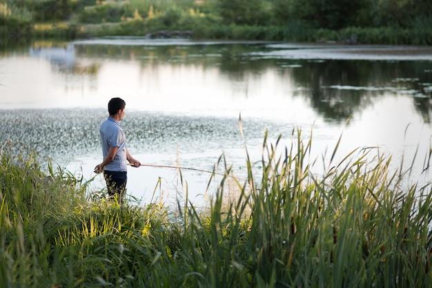 녹색 호수 은행에서 저녁 낚시에 막대를 든 어부