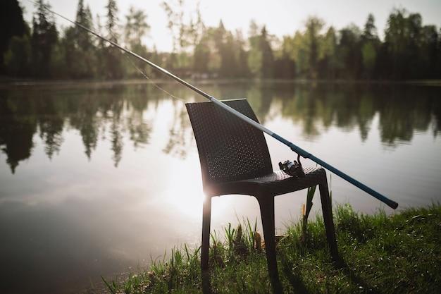 Удочка лежит на стуле, который стоит вечером на берегу озера