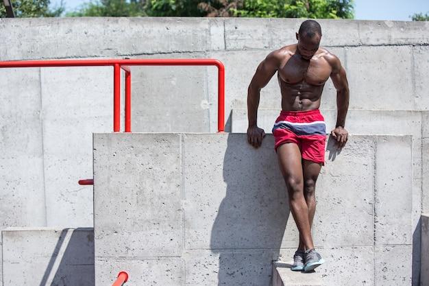 エクササイズをしている健康なアスリート。街で屋外のアフロまたはアフリカ系アメリカ人の男。スポーツエクササイズを引き上げます。