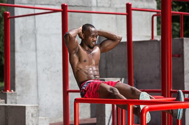 スタジアムでエクササイズをしている健康なアスリート。街で屋外のアフロまたはアフリカ系アメリカ人の男。スポーツエクササイズを引き上げます。フィットネス、健康、ライフスタイルの概念