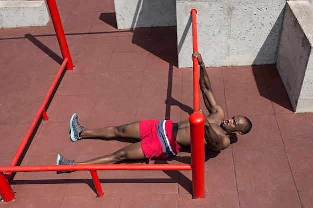 Фитнес спортсмен делает упражнения на стадионе. афро или афро-американский мужчина на открытом воздухе в городе. подтягивание спортивных упражнений. фитнес, здоровье, концепция образа жизни