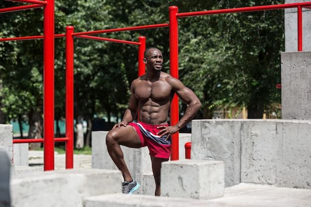 Фитнес спортсмен делает упражнения на стадионе